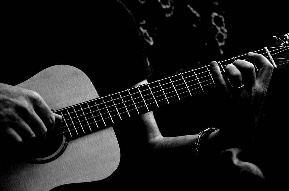 Monochrome Photo of Person Playing Acoustic Guitar