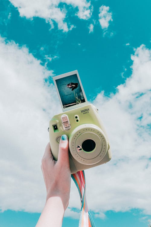Person Holding Instant Camera With Photo
