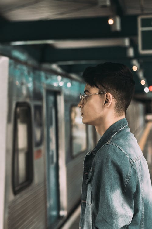 Side View Portrait Photo of Man Standing on Subway Platform by Train