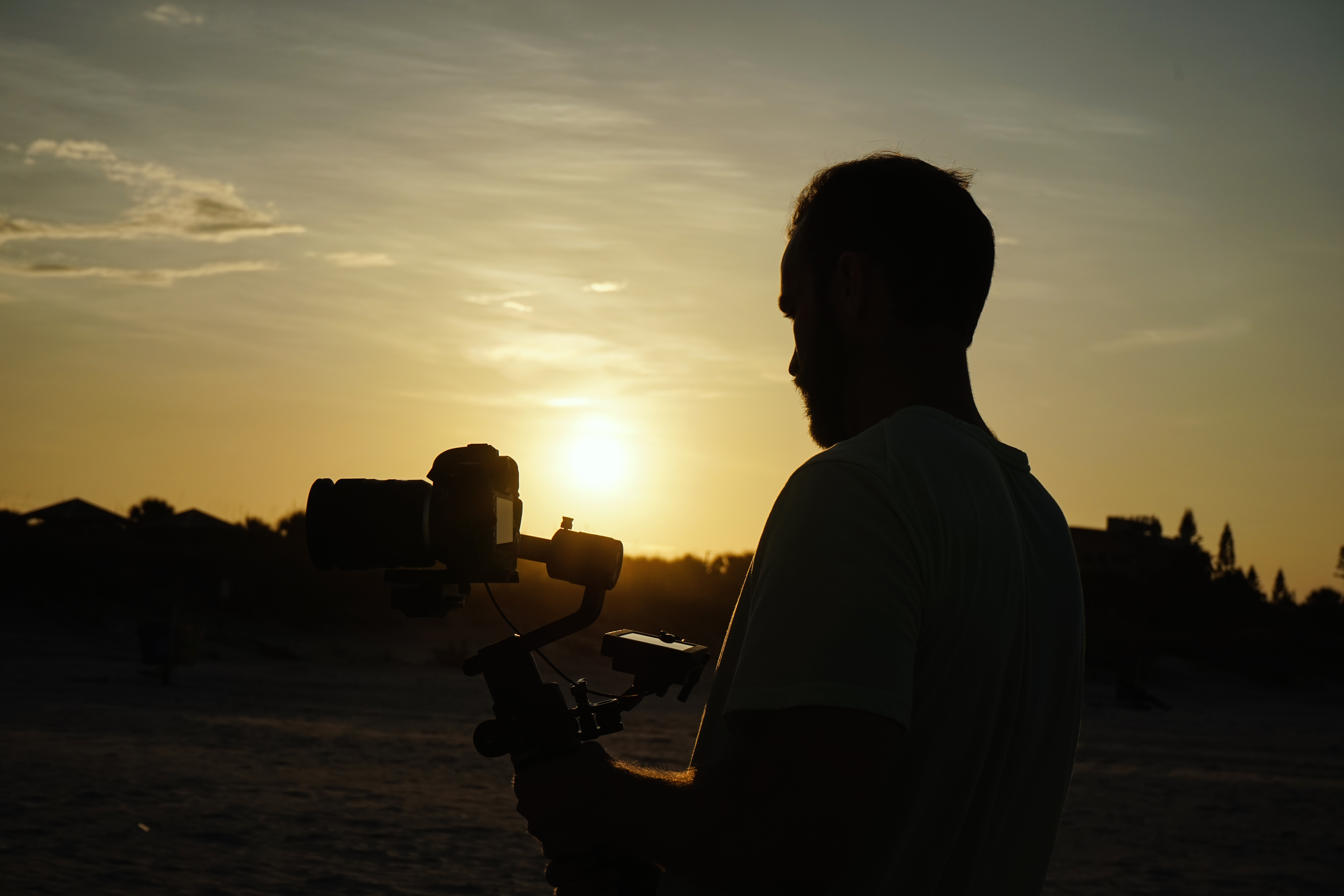 silhouette photo of man holding camera during golden hour
