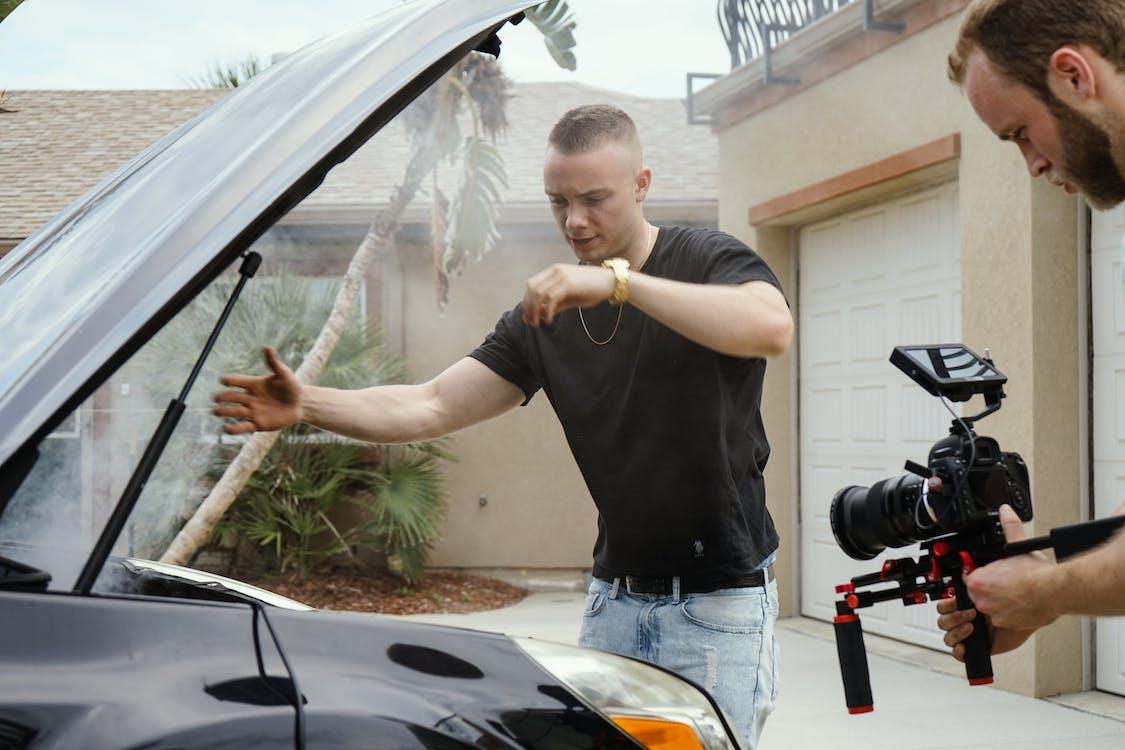 Man Wearing Black Shirt Looking at Car Engine Bay