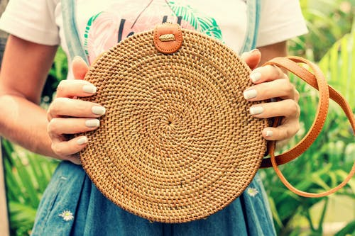 Close-up Photo of a Round Brown Rattan Bag Held by Woman