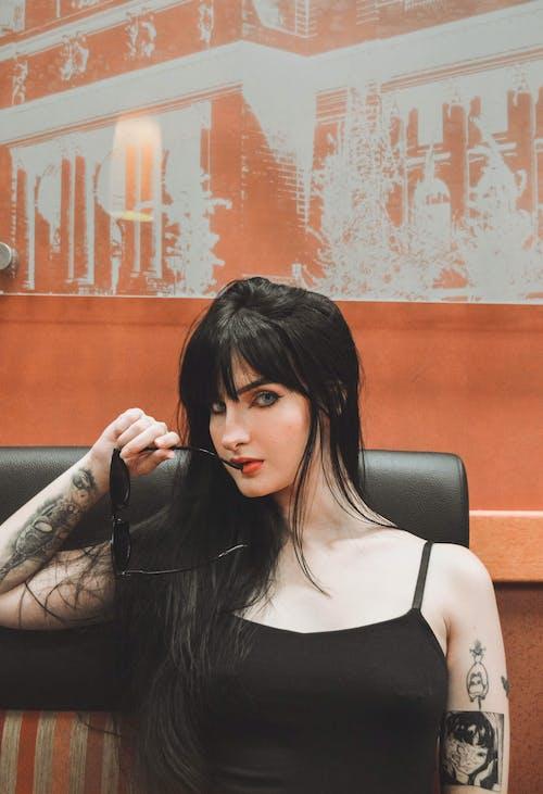 Portrait Photo of Tattooed Woman Sitting Near Orange Wall Posing With Sunglasses