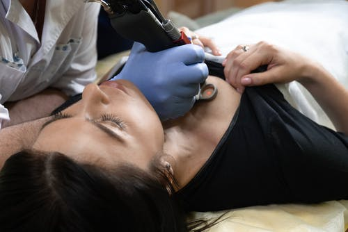 Woman in Black Shirt Being Tattooed in Chest