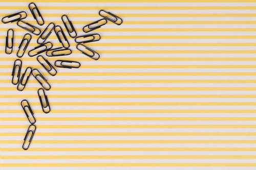 Бесплатное стоковое фото с желтые полосы, скрепки, черные скрепки