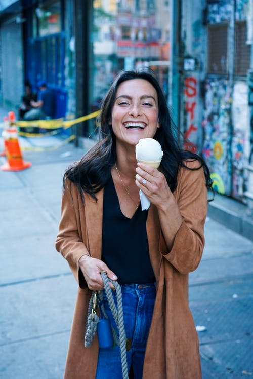 Woman Wearing Brown Trench Coat While Holding Ice Cream
