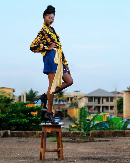 Woman in Black and Yellow Top and Blue Skirt Standing on Brown Wooden Stool