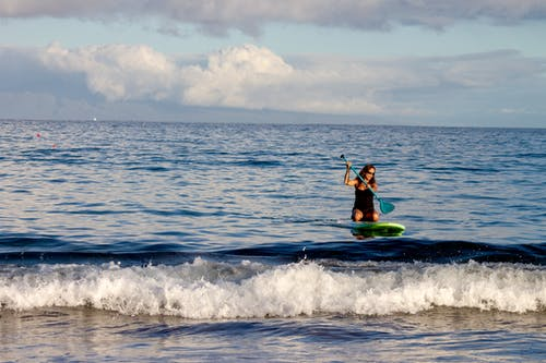 Woman Riding Green Surfboard Using Paddle