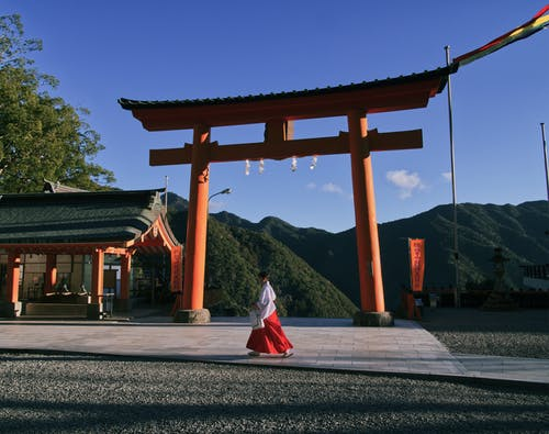 Woman Wearing Red and White Dress walking near a Shinto shrine