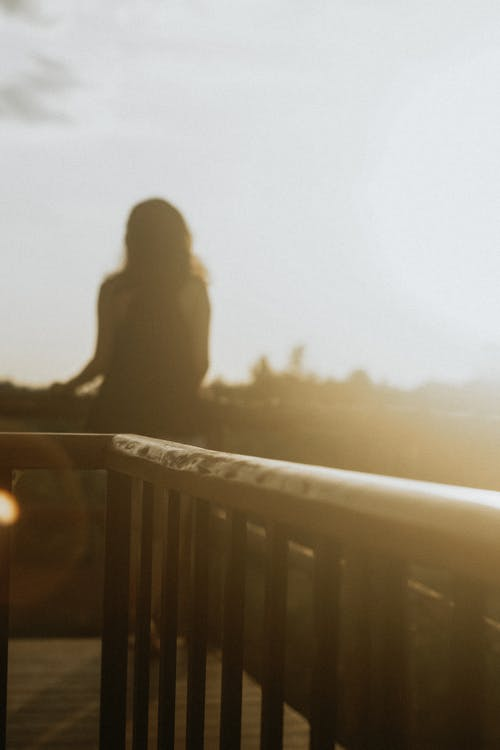 Silhouette of Person Standing On Balcony