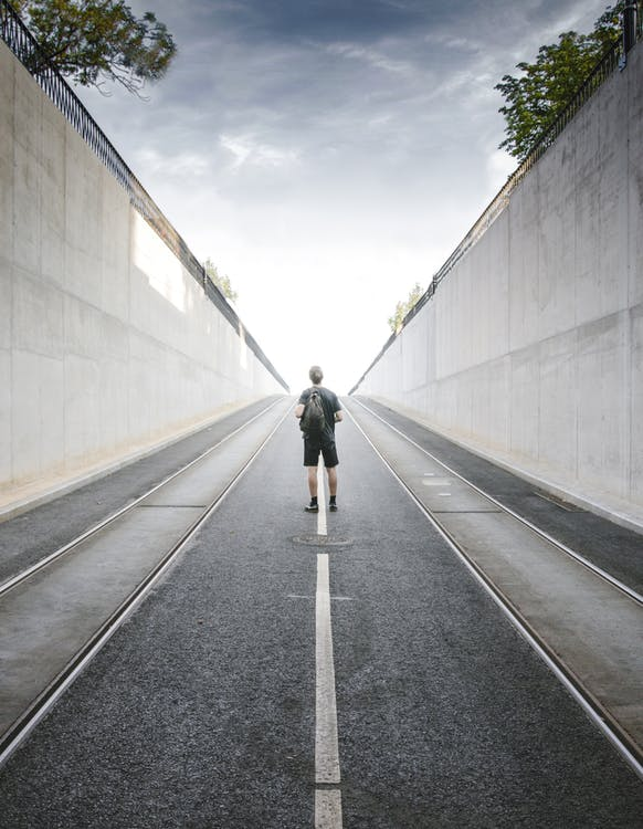 Backview of a man man standing in the middle of the road