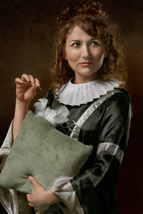 Photo of Woman Ripped Holding Throw Pillow in One Hand and Needle with Thread in the Other