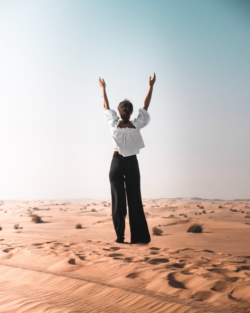 Back View Photo of Woman With Her Hands Up Standing on Desert Sand