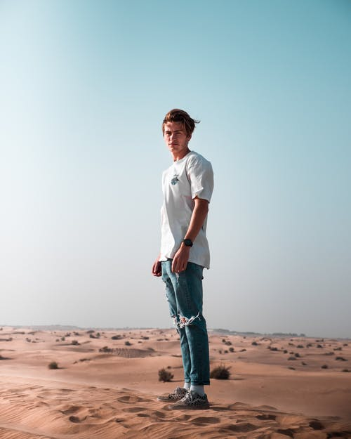 Man wearing a white t-shirt and blue denim pants standing on sand