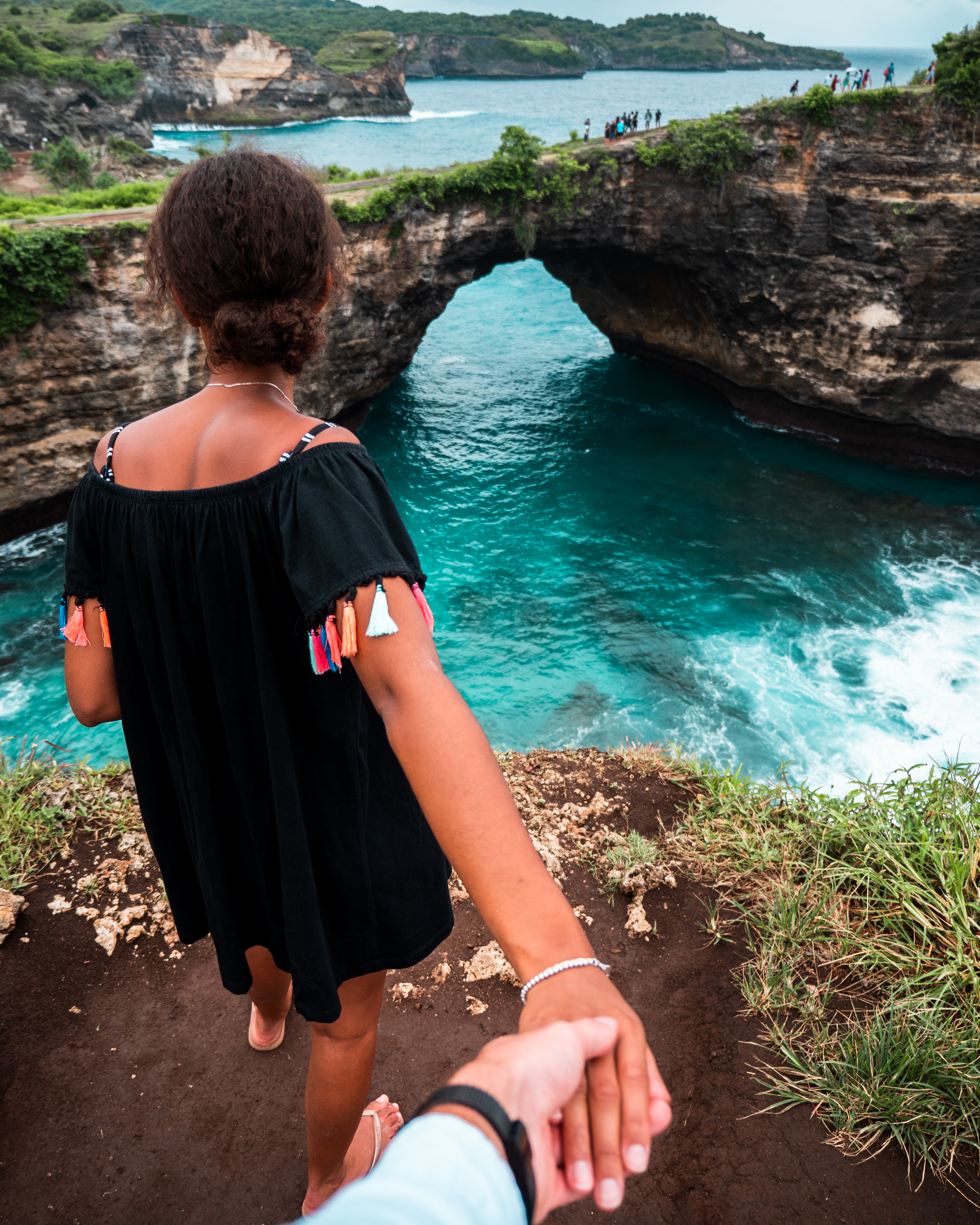 Person Holdings Woman Hand in Front of Body of Water