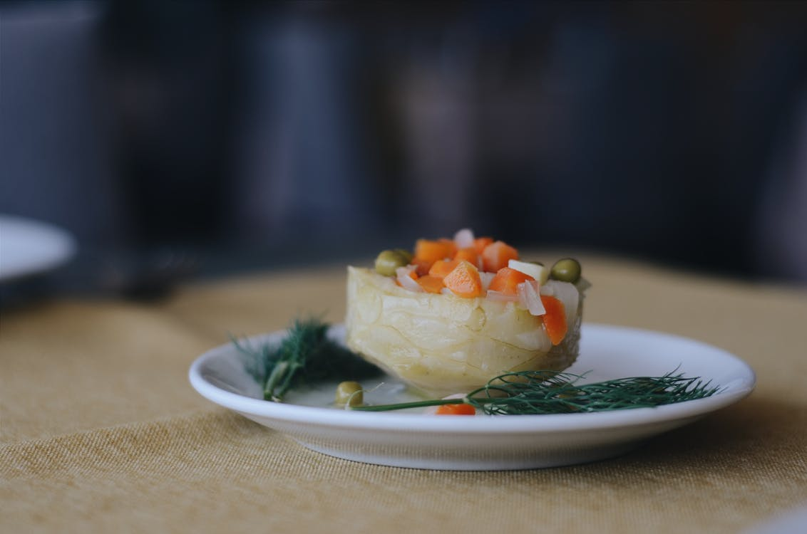 Photo of Cooked Green peas,Carrots and Rosemary leaves on a White Plate