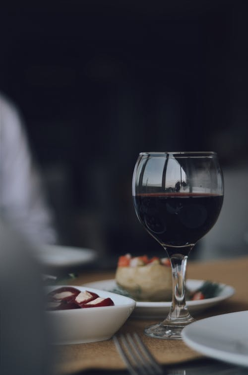 Selective Focus Photo of Red Wine in Wine Glass