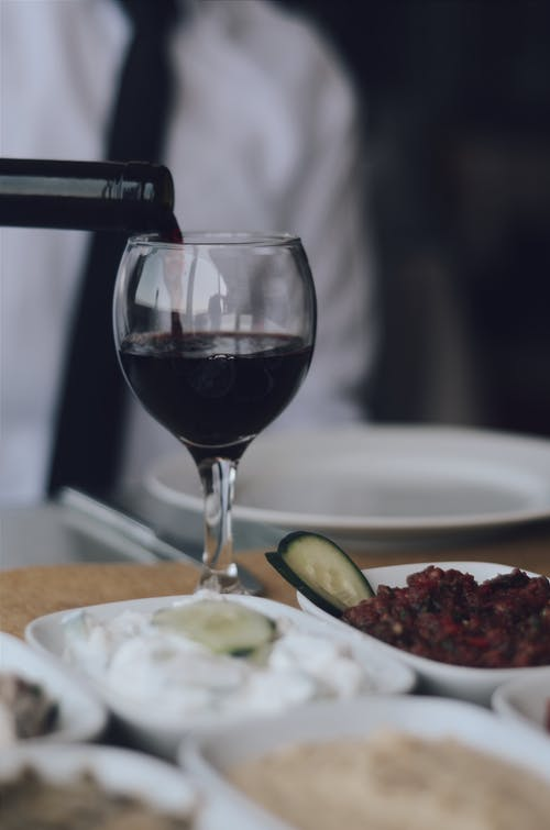 Blurry Photo of a Person Pouring Red Wine in Wine Glass Beside Assorted Foods