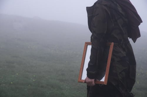 Close Up Photo of Person in a Jacket Holding Brown Wooden Framed Mirror