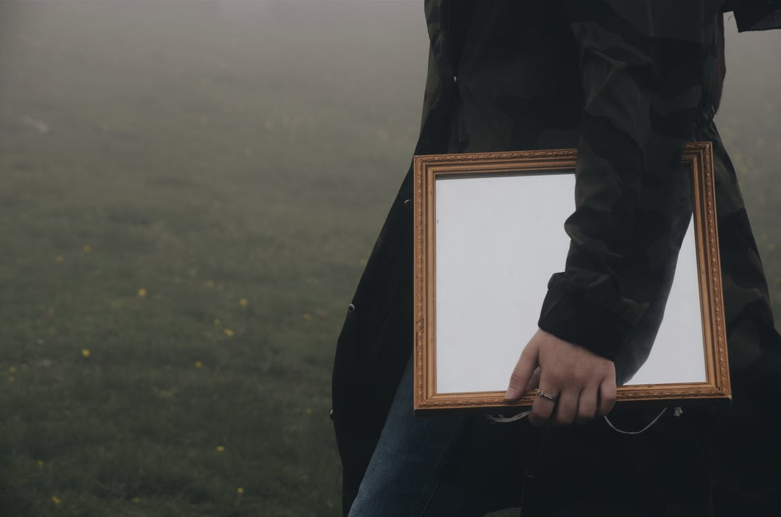 Close Up of Person Wearing Long Jacket  Carrying Brown Framed Mirror