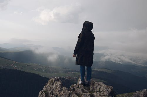 Person Wearing Black Jacket Standing on Mountain Edge