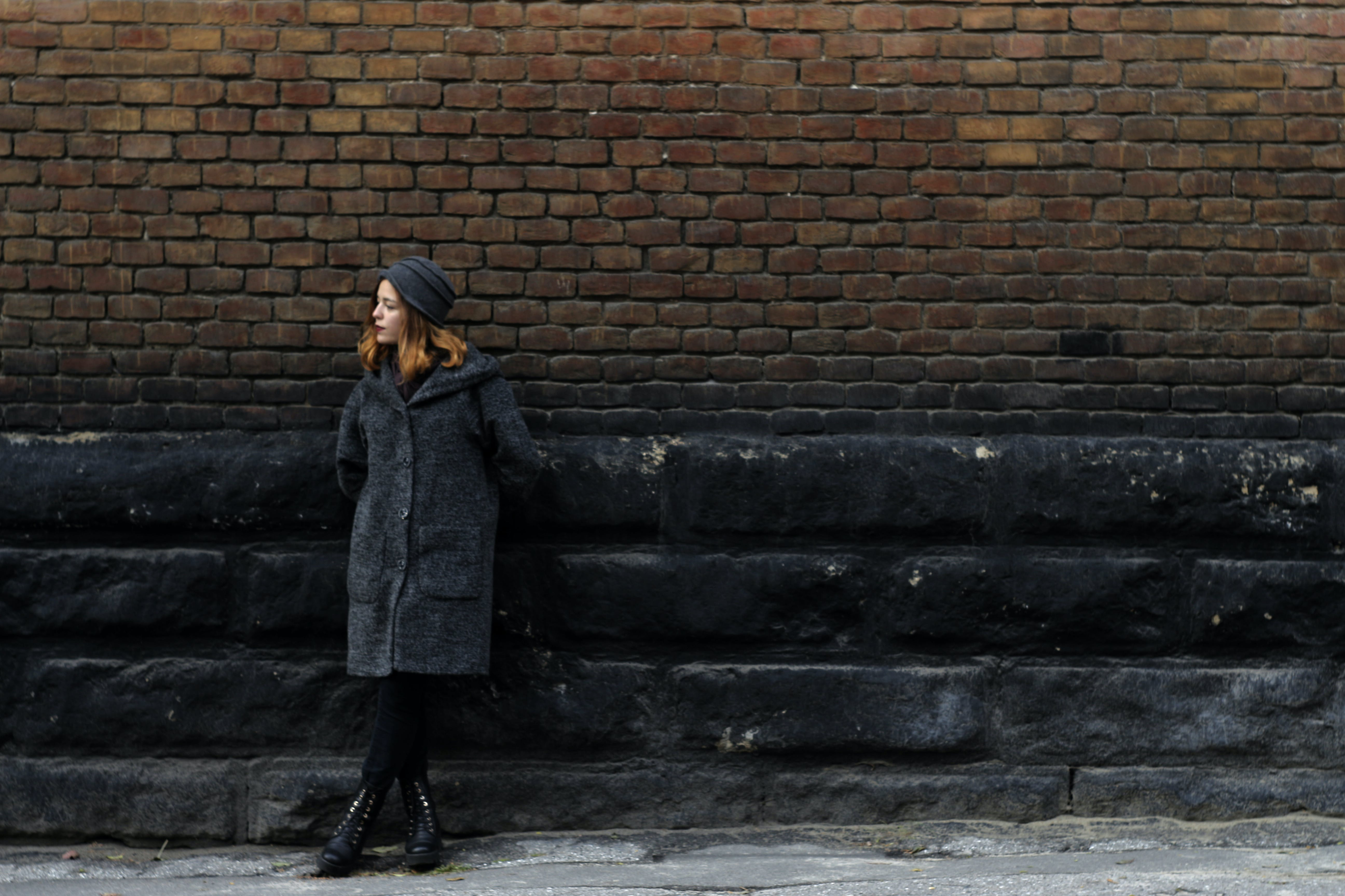 Woman Wearing Grey Coat Standing in Front of Brown Brick Wall