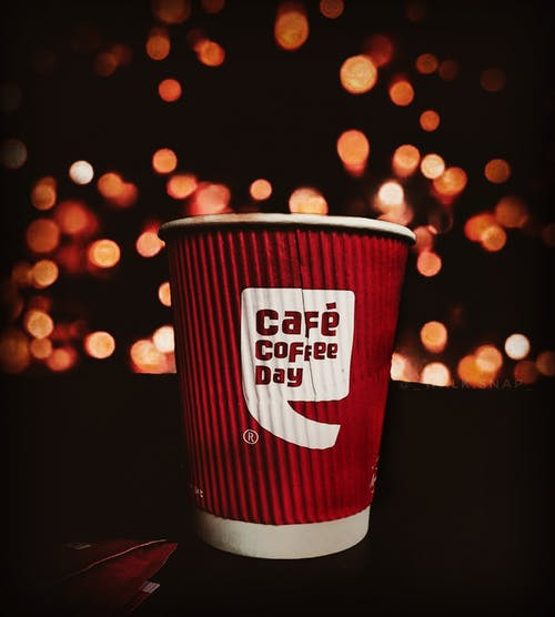 Selective Focus Photo of Red and white Cafe Coffee Day Disposable Paper  Cup