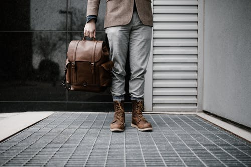 Photo of Man in Brown Blazer,Gray Pants, and Brown Boots Holding Brown Leather Bag Standing Outside Building