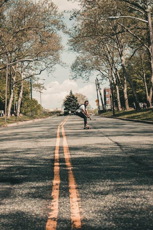 Darmowe zdjęcie z galerii z akcja, droga, drzewa, jazda na deskorolce