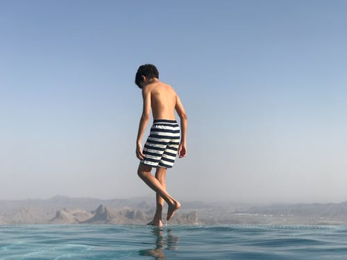 Back View Photo of Boy in Swimming Trunks Standing on the Edge of an Infinity Pool