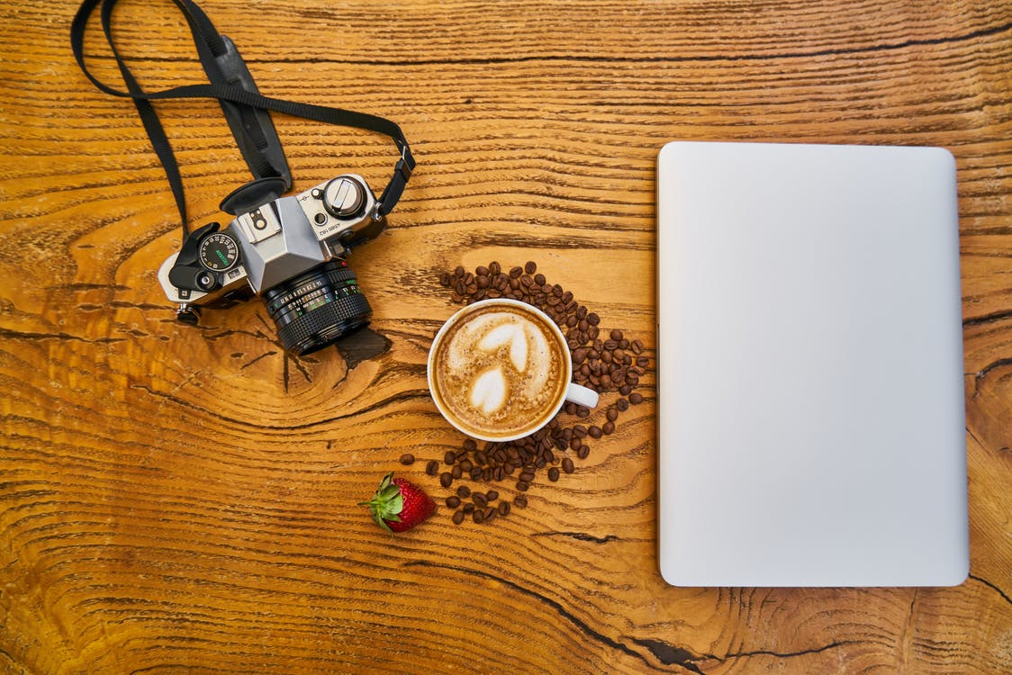 Latte Coffee And Camera On Wooden Surface