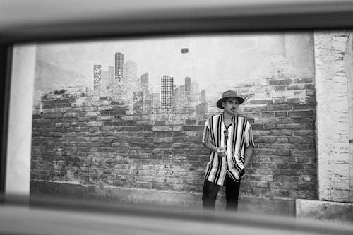 Monochrome Photo of Man Leaning on Brick Wall