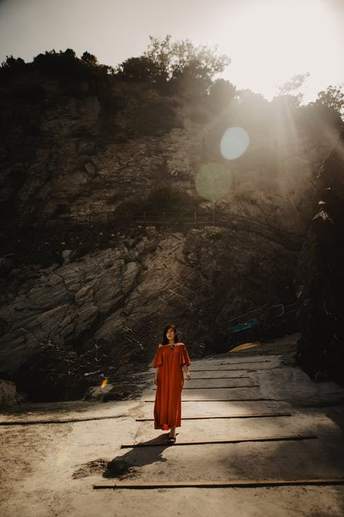Woman in Orange Dress Standing on Pathway Below A Rock Formation