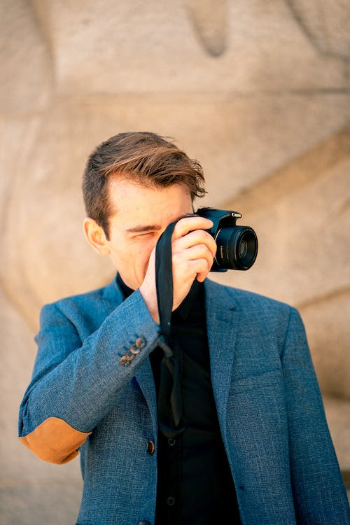 Photo of Man in Black Shirt and Blue Blazer Taking a Photo