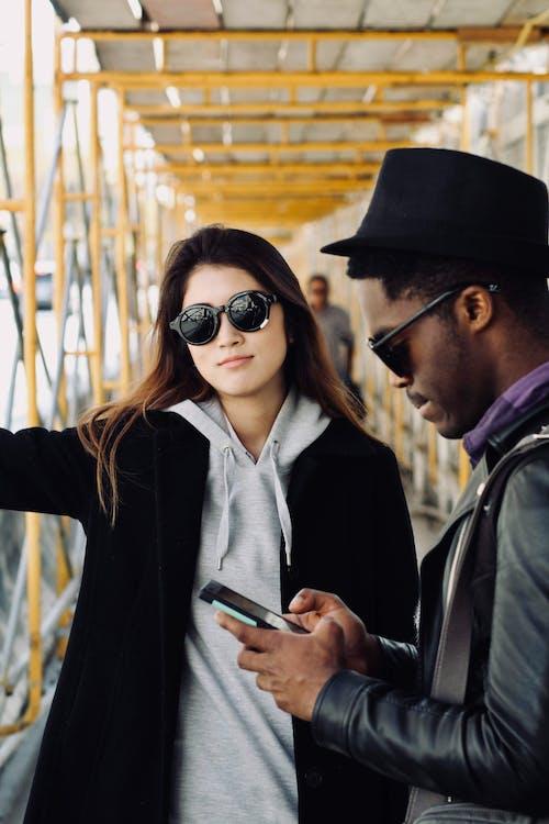 Smiling Woman Standing Beside Man Using Smartphone