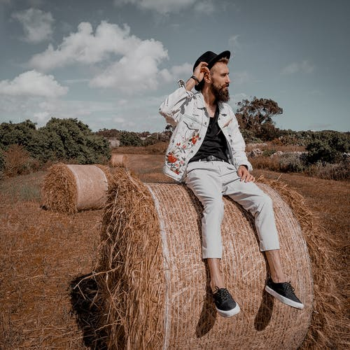 Man Sitting On A Roll Of Hay