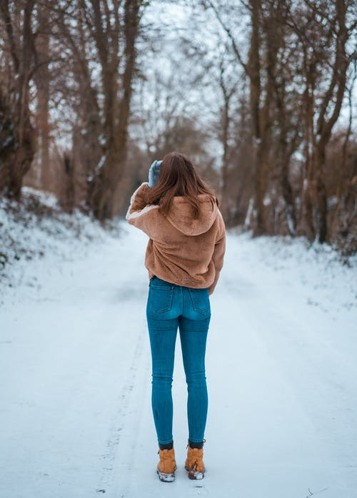 Woman Standing on Snow Covered Ground
