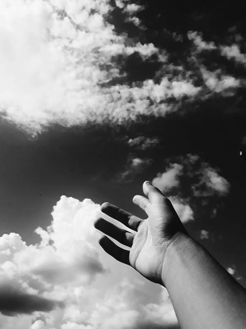 Grayscale Photo Of Person Raising Hands Towards the Sky
