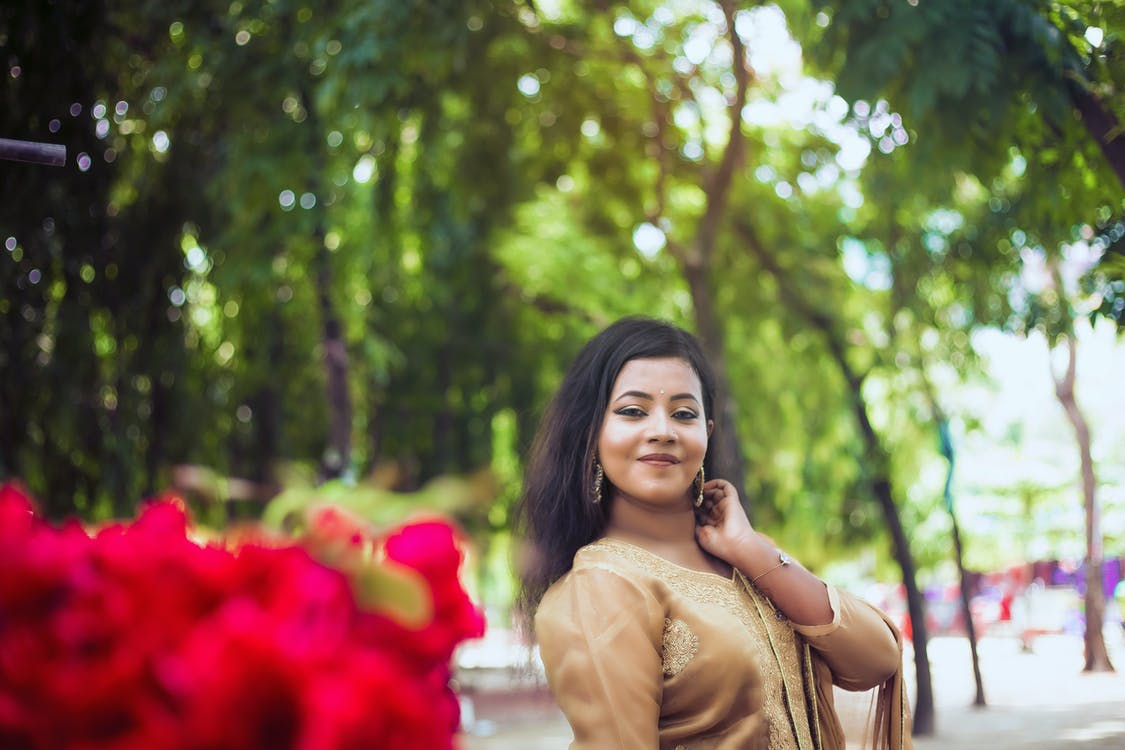beautiful woman, green trees, in front of red roses blurred