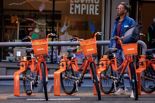 Man Standing Behind Parked Orange Bicycles