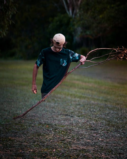 Man Holding Leafless Tree Branch