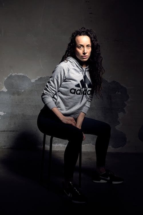 Woman In Grey Adidas Pullover Hoodie Sitting On Black Stool