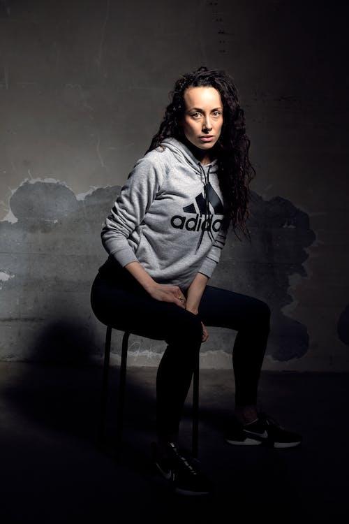 Woman In Grey Adidas Pullover Hoodie Sitting On Black Stool