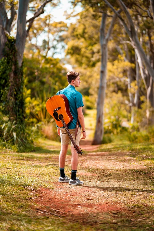 Back View Photo of Man Acoustic Carrying Guitar Standing Alone on Trail Looking to His Right