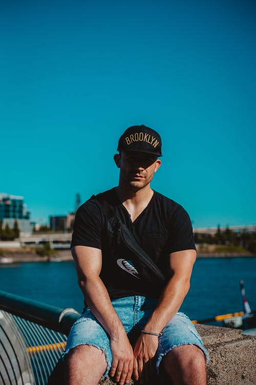 Photo of Man in Black Cap, T-shirt, and Blue Denim Shorts Sitting on Concrete Surface Posing with Body of Water in the Background