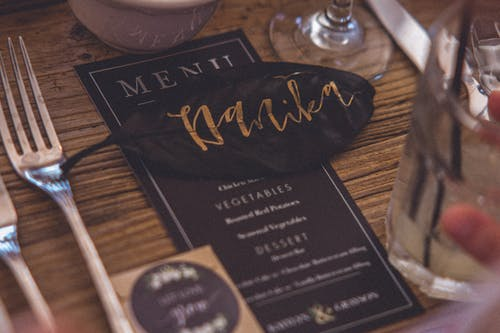 Brown Leaf With Text Placed over the Menu Between Glass Cup and Fok