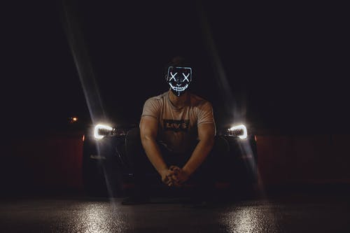 Photo of Man Wearing Mask in Front of Car