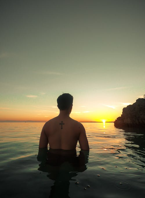 Man Dipped In The Sea During Golden Hour
