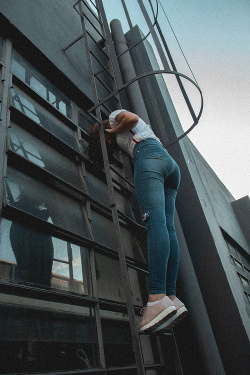 Photo of Woman Standing on Ladder
