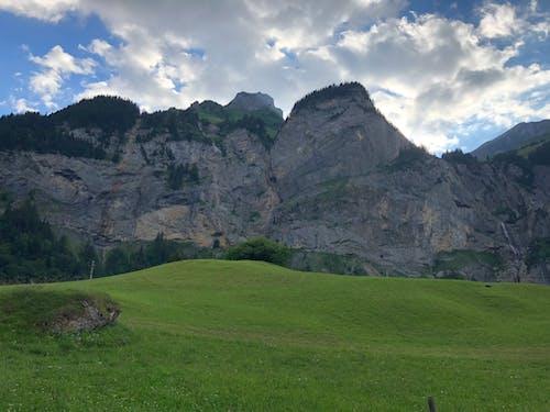 çim saha, dağ içeren Ücretsiz stok fotoğraf